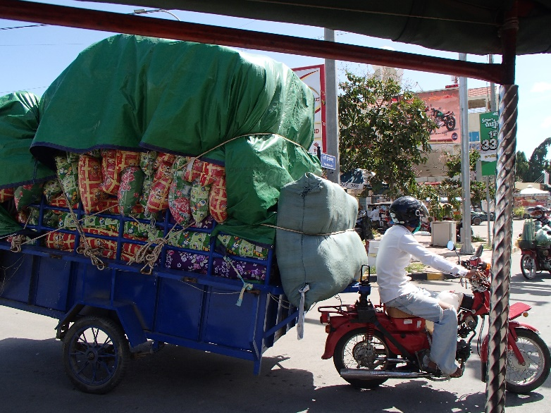 A man on a motorbike hauls a colorful load strapped in with rope and a bright-green tarp.