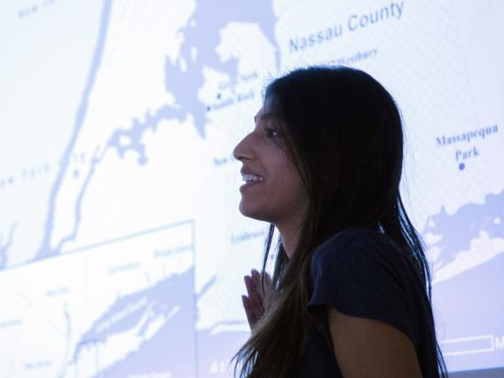 Female student presenting in front of projected map